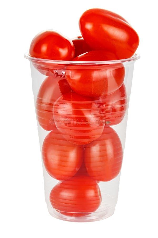 Tomates de cereja, frescos e maduros, num copo de plástico transparente descartável, isolados sobre fundo branco foto de stock royalty free