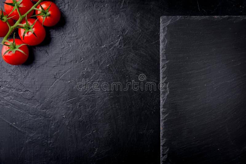 Tomates de cereja frescos em um fundo preto com placa da ardósia Vista superior com espaço da cópia fotos de stock