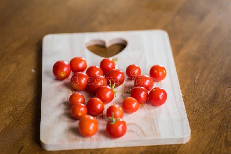 Tomates de cereja frescos em uma placa de corte de madeira imagens de stock