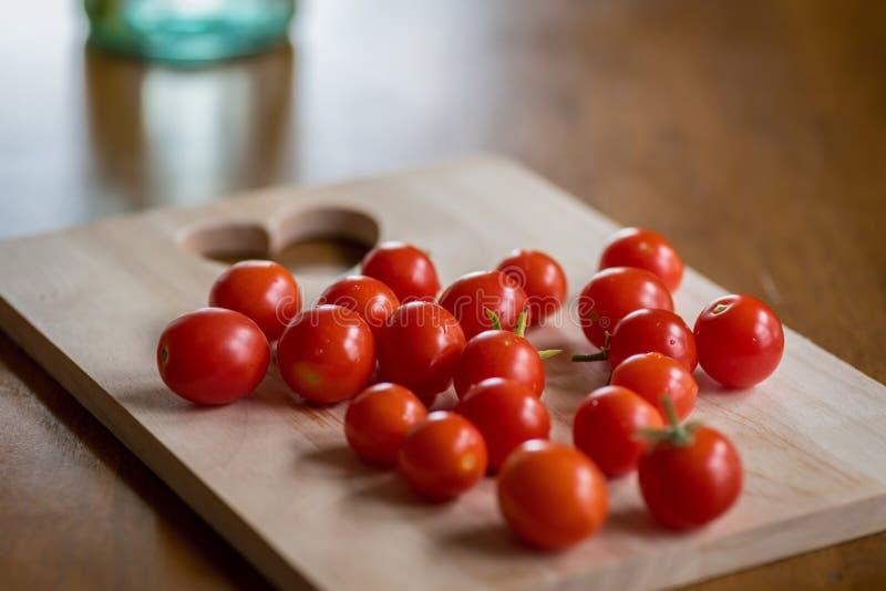 Tomates de cereja frescos em uma placa de corte de madeira imagem de stock