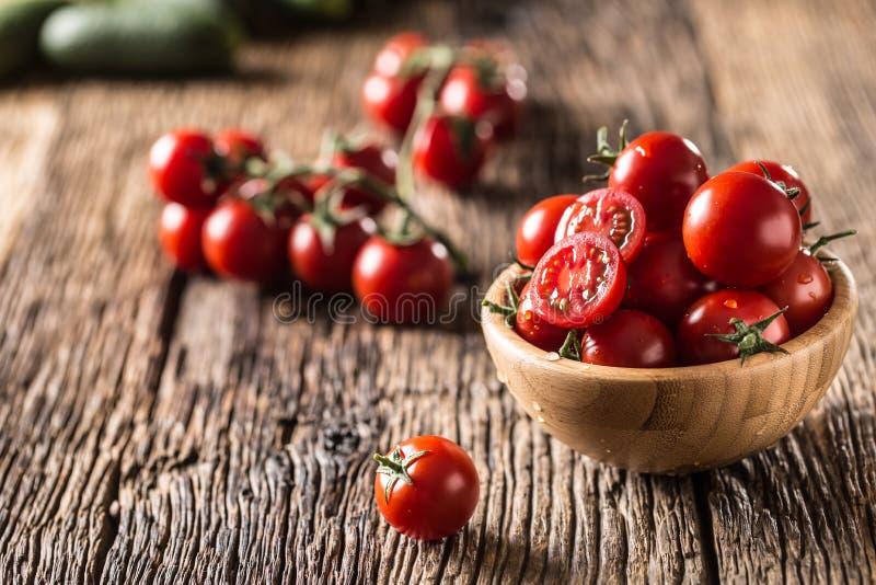 Tomates de cereja frescos na bacia de madeira na tabela de carvalho velha fotografia de stock royalty free