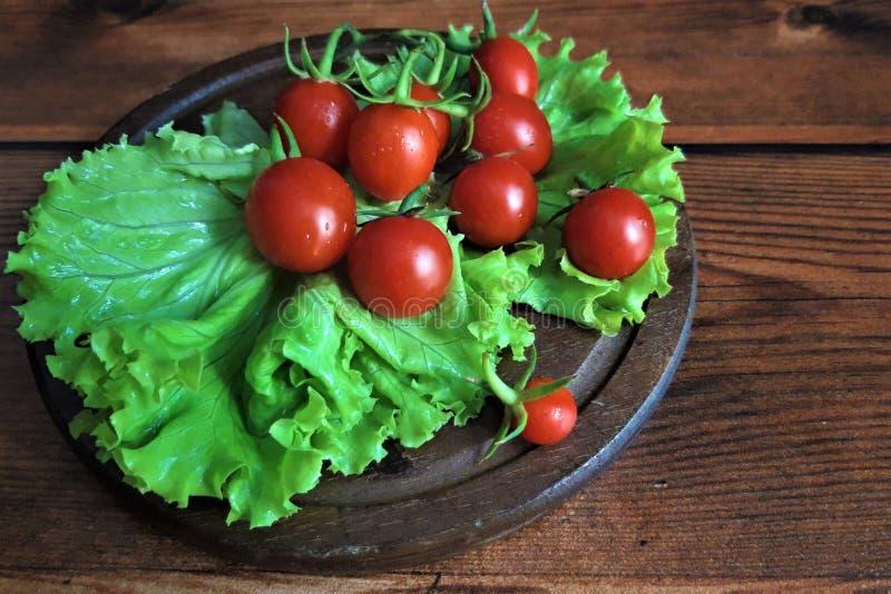 Tomates de cereja frescos, salada verde, de madeira fotos de stock