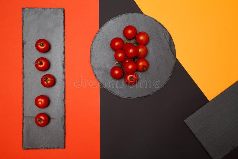 Tomates de cereja maduros compostos em placas pretas da ardósia no fundo colorido foto de stock royalty free