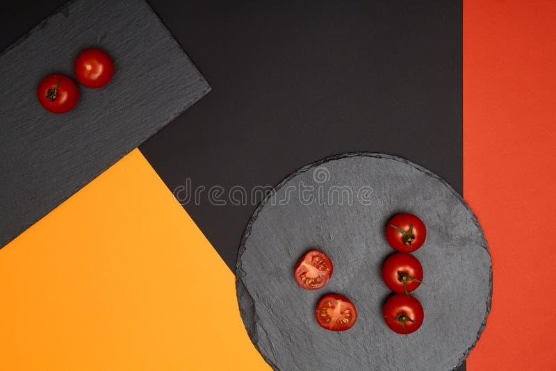 Tomates de cereja maduros compostos em placas pretas da ardósia no fundo colorido fotos de stock