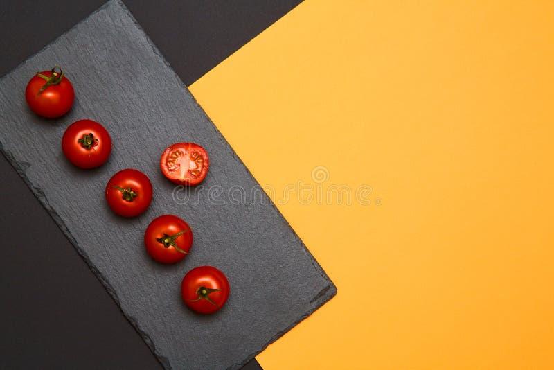 Tomates de cereja maduros compostos em placas pretas da ardósia no fundo colorido foto de stock