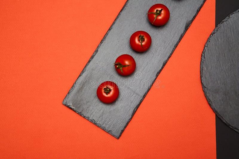 Tomates de cereja maduros compostos em placas pretas da ardósia no fundo colorido fotografia de stock royalty free