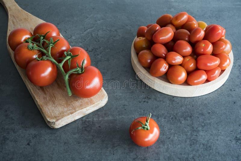 Tomates de cereja na placa e na placa de corte de madeira, foto de stock