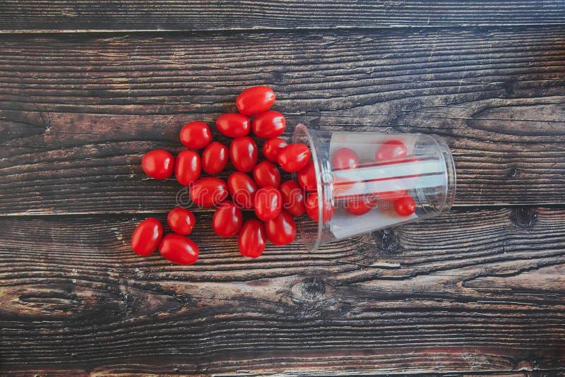 Tomates de cereja pequenos em um frasco em uma tabela de madeira preta foto de stock