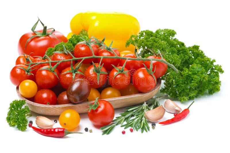 Tomates de cereza coloreados en un cuenco de madera, pimienta, hierbas fotografía de archivo