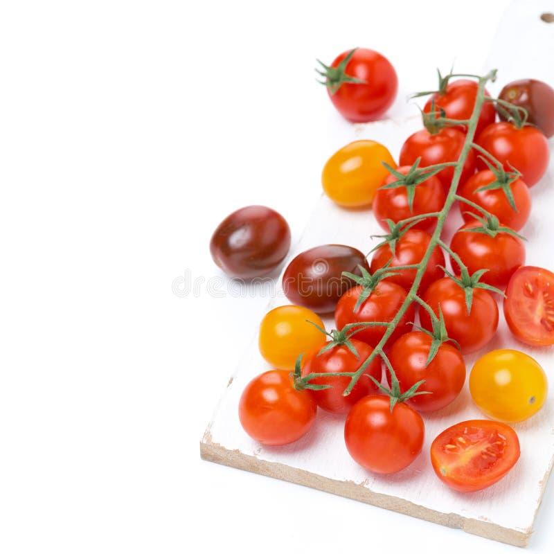 Tomates de cereza coloridos en el tablero blanco foto de archivo libre de regalías