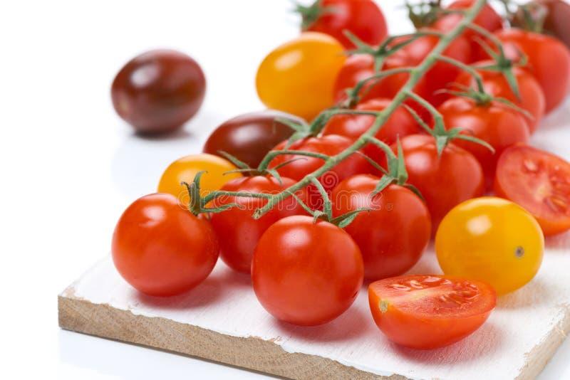 Tomates de cereza coloridos en un tablero de madera, primer, aislado fotos de archivo libres de regalías