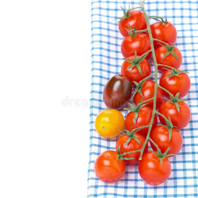 Tomates de cereza coloridos en una servilleta azul, aislada imagen de archivo libre de regalías