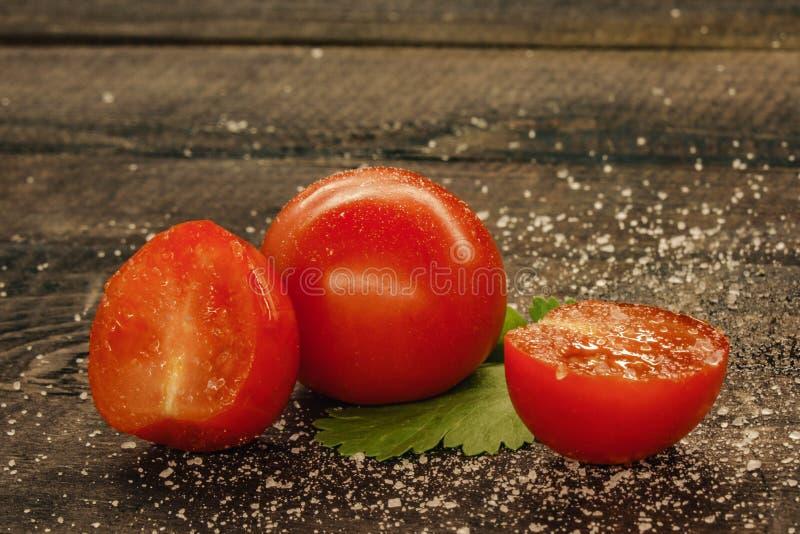 tomates de cereza deliciosos asperjados con la sal en un fondo de madera foto de archivo libre de regalías