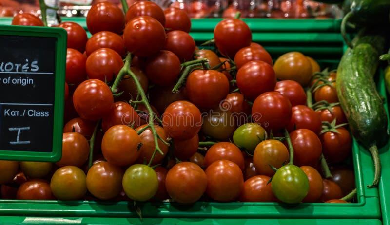 Tomates de cereza en cesta en el supermercado, visión de primera persona imagenes de archivo