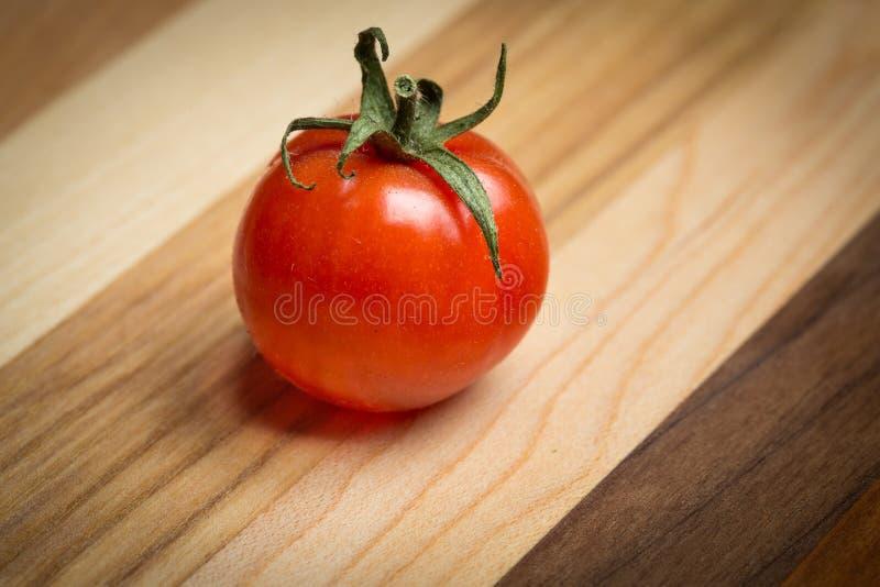 tomates de cereza en tabla de cortar de madera imagen de archivo libre de regalías