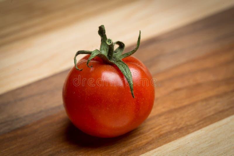 tomates de cereza en tabla de cortar de madera fotografía de archivo libre de regalías