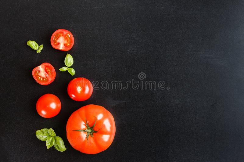 Tomates de cereza frescos en un fondo negro de la pizarra con la hierba imagenes de archivo