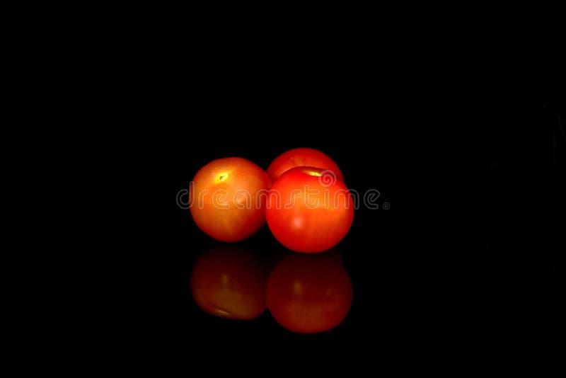 Tomates de cereza rojos aislados en el fondo negro fotos de archivo libres de regalías