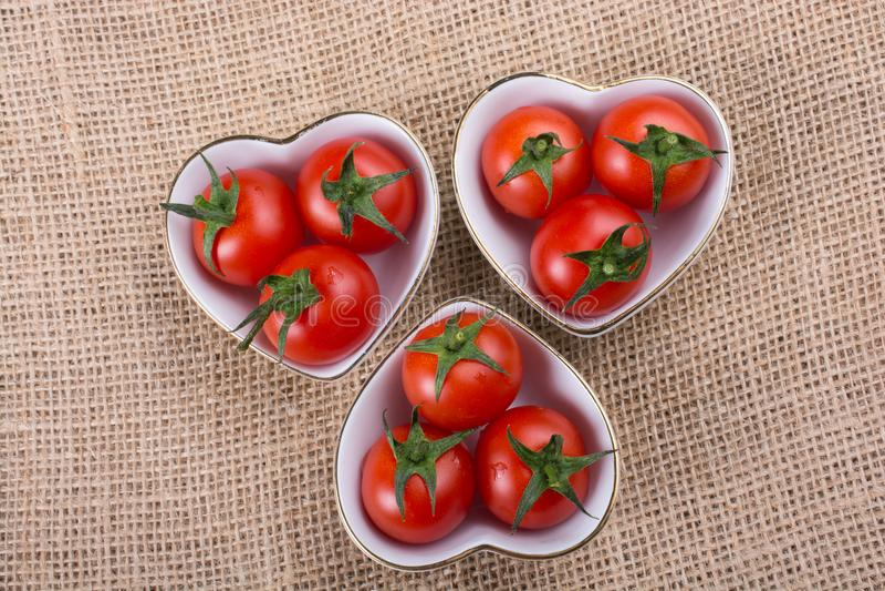 Tomates de cereza rojos en cuenco en forma de corazón imagenes de archivo