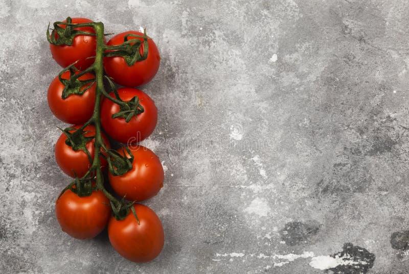 Tomates de cereza rojos en fondo gris Visión superior; copie el espacio FO fotos de archivo libres de regalías