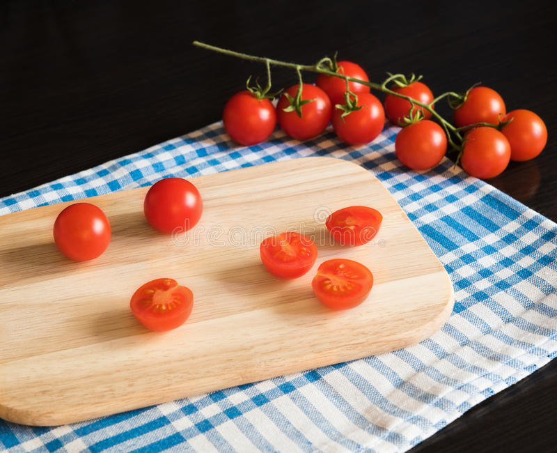 Tomates de cereza rojos en tabla de cortar foto de archivo