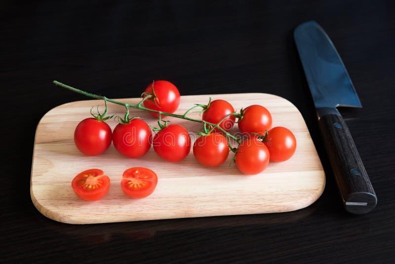 Tomates de cereza rojos en tabla de cortar imagen de archivo libre de regalías