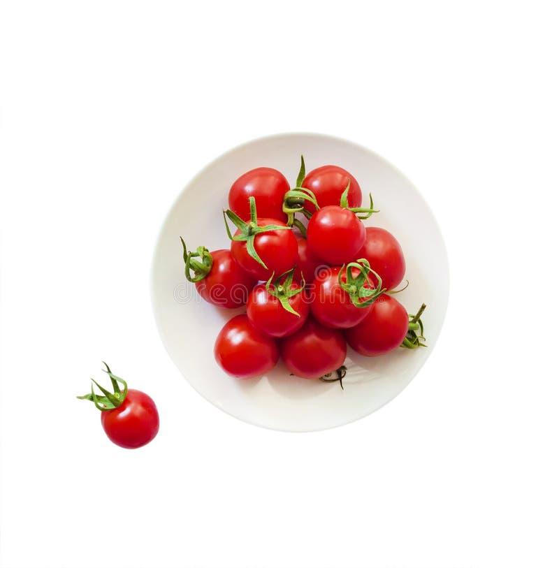 Tomates de cereza rojos en una placa aislada imagenes de archivo