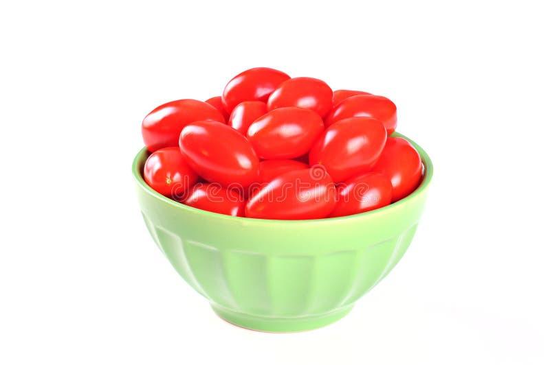 Tomates de cereza sabrosos en un cuenco, fondo blanco fotos de archivo libres de regalías