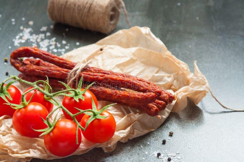 Tomates de cereza y sauseges secados en una tabla de piedra foto de archivo