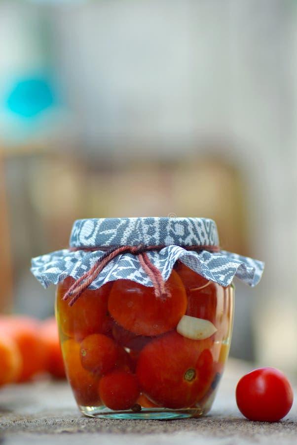 Tomates de colocação em latas foto de stock