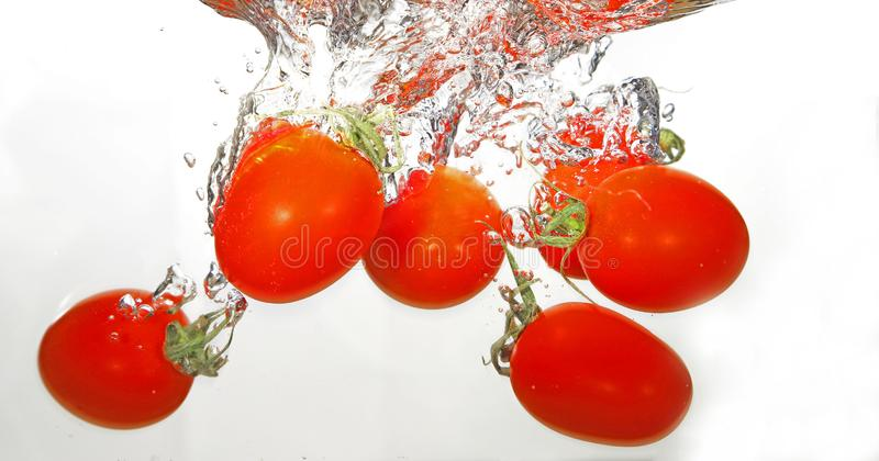 Tomates de la uva en el agua imagenes de archivo