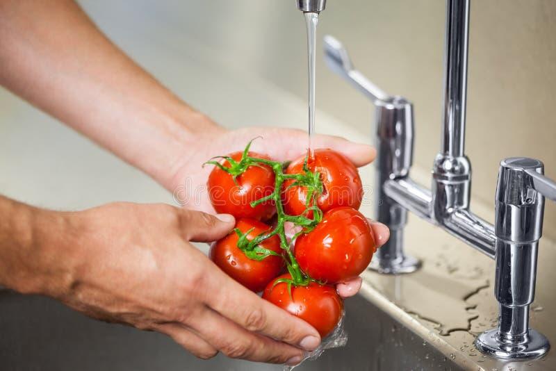 Tomates de lavage de portier de cuisine sous le robinet fonctionnant image libre de droits