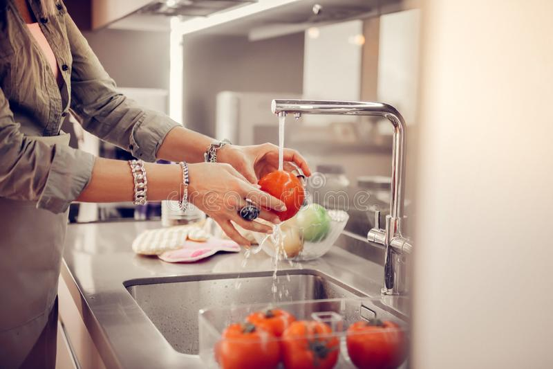 Tomates de lavagem da mulher superior agradável no dissipador imagem de stock