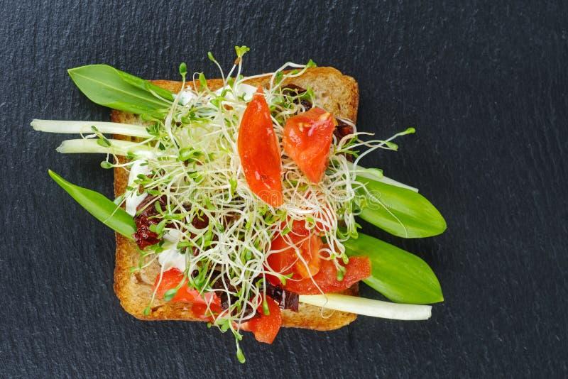 Tomates de pousses de luzerne, fraîches et séché vertes sur les tranches grillées de pain entier d'isolement sur la pierre noire images stock