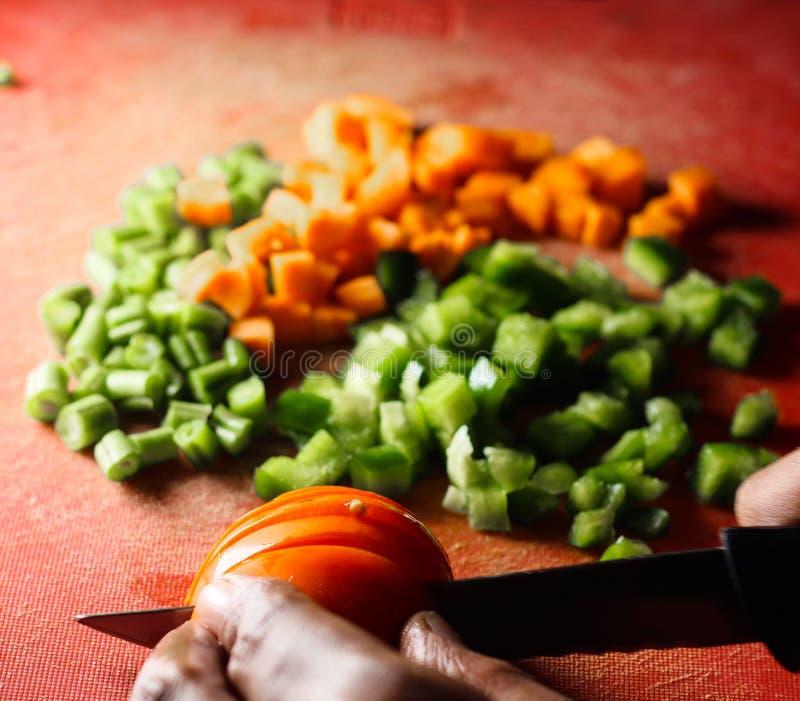Tomates do capsicum e corte da cenoura em partes pequenas, finamente - vegetais desbastados em uma placa de desbastamento pela fa imagem de stock royalty free
