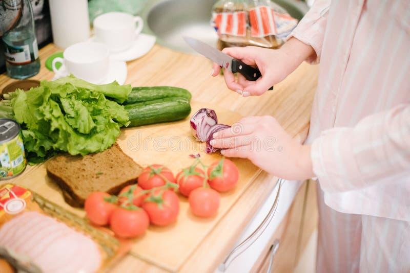Tomates dos cortes do homem e outros vegetais com uma faca em uma placa de corte de madeira imagem de stock