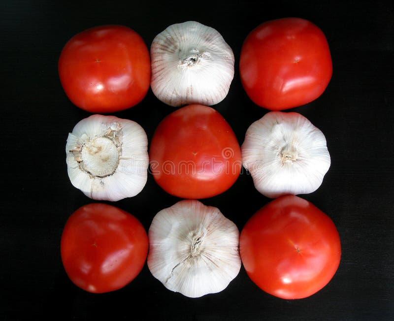 Tomates e alho no teste padrão fotografia de stock royalty free