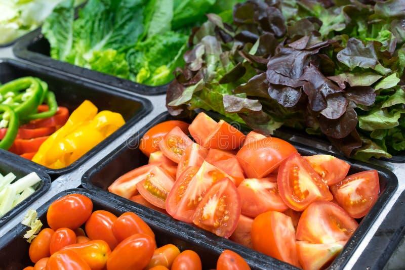 Tomates e outros vegetais em bandejas da salada imagem de stock royalty free