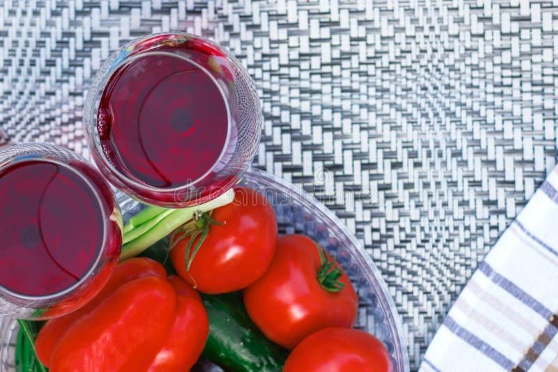 Tomates e pimentos frescos em um fundo abstrato Vinho vermelho em um vidro imagem de stock
