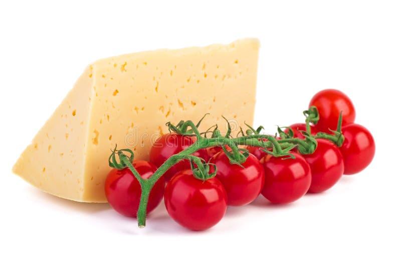 Tomates e queijo em uma placa de corte de madeira fotografia de stock royalty free