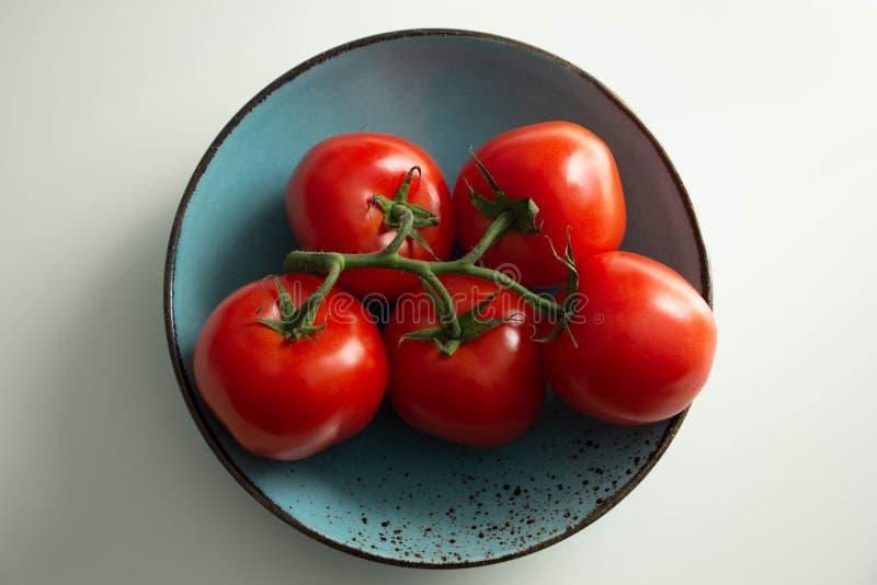 Tomates em um ramo em uma placa de turquesa fotos de stock royalty free