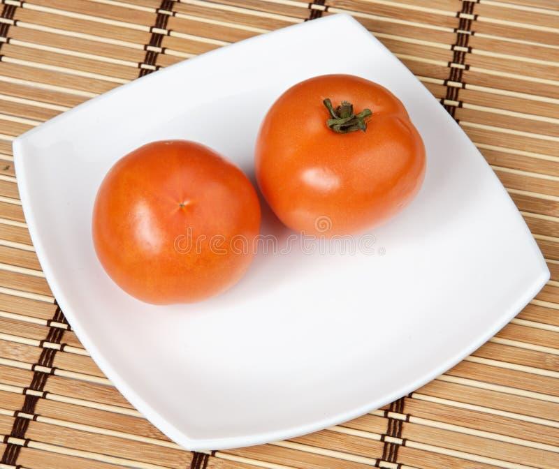 Tomates em uma placa fotografia de stock royalty free