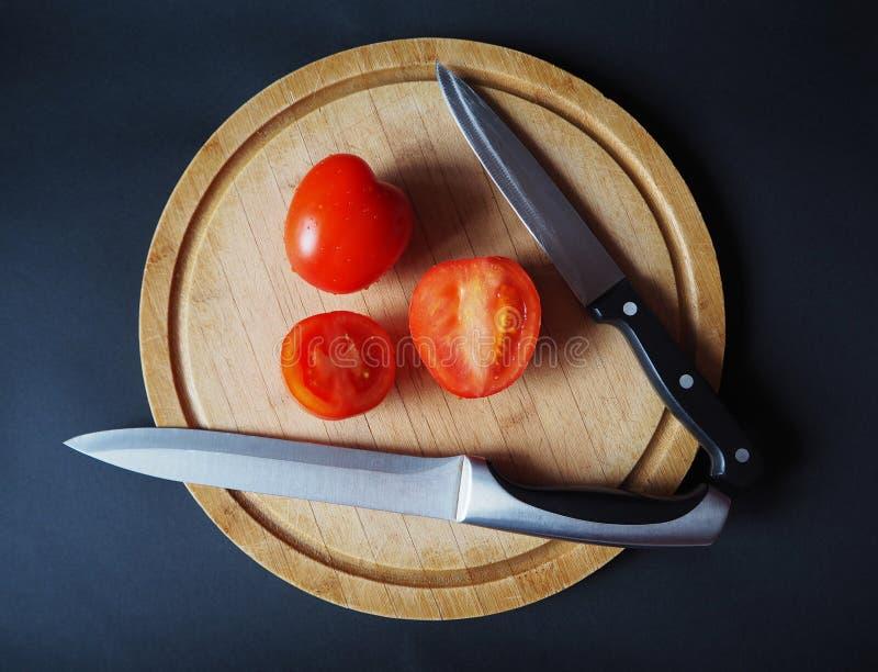 Tomates en la tabla de cortar de madera redonda con la opinión superior de dos cuchillos fotos de archivo libres de regalías
