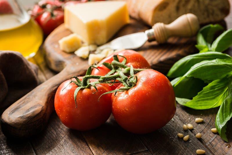 Tomates en la vid, el aceite de oliva y el queso parmesano, fondo de la comida fotografía de archivo