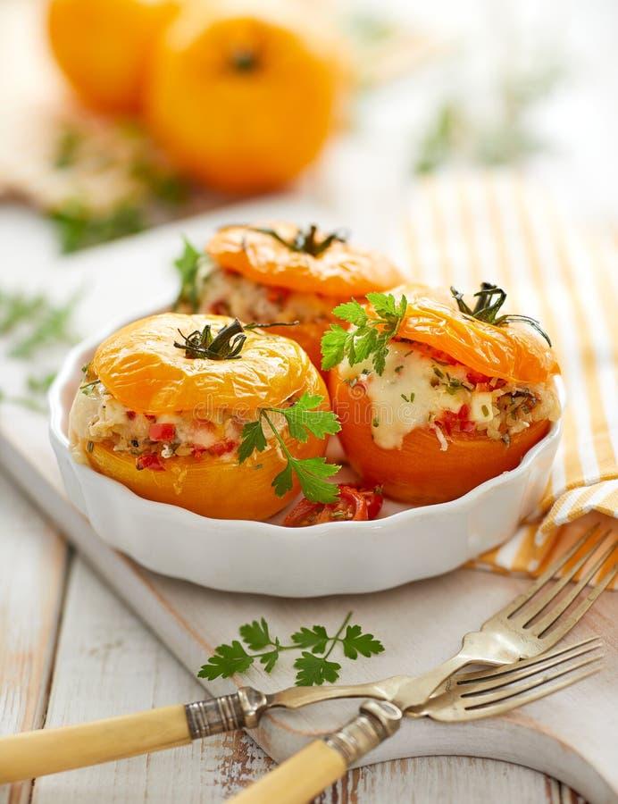 Tomates enchidos, tomates amarelos cozidos enchidos com bulgur, vegetais e queijo com a adição de ervas aromáticas em um coziment fotos de stock