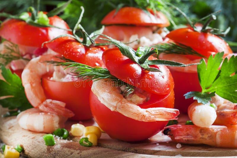 Tomates enchidos com carne do camarão e milho em uma placa de madeira, SE fotografia de stock