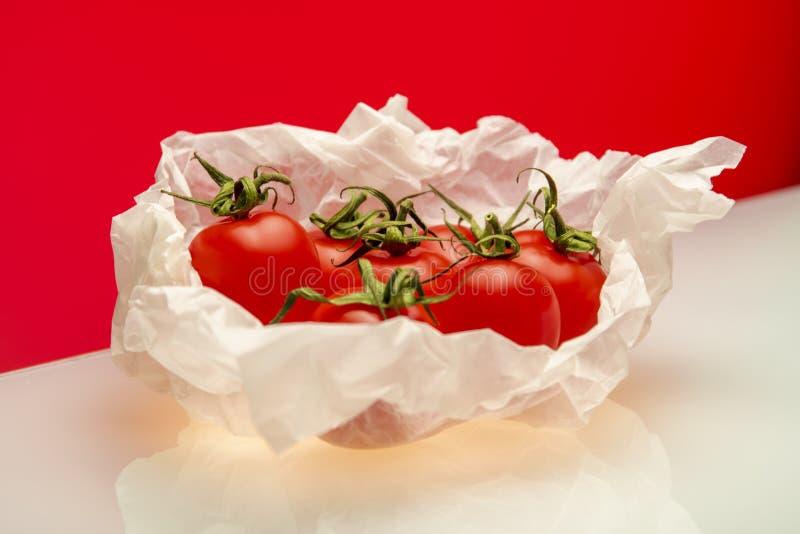 Tomates envolvidos em cozinhar o papel no fundo vermelho fotos de stock royalty free