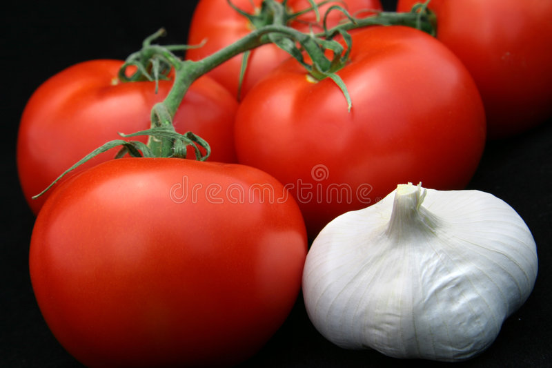 Tomates et ail sur le noir photos libres de droits