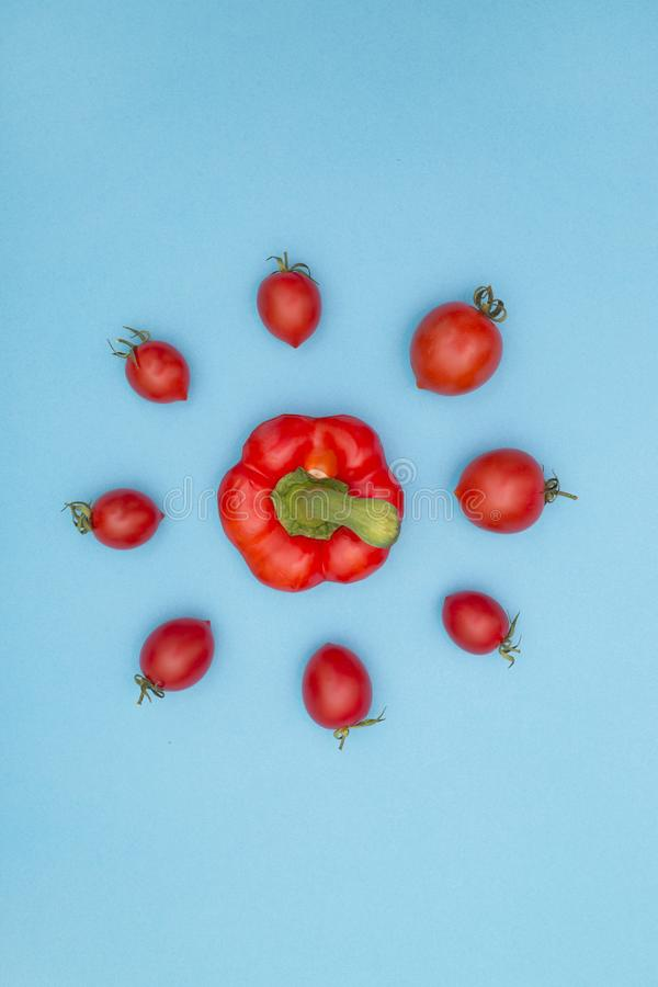 Tomates et dessus mûrs rouges de poivron doux sur un fond bleu images stock