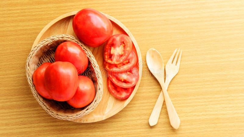 Tomates fra?ches et de tranche plac?es sur un plat en bois La cuill?re et la fourchette s'?tendent sur une table en bois cuisson  image libre de droits